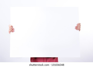 Business woman holding big blank white poster board to her face, isolated on white background.