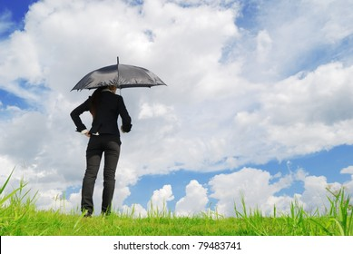 Business woman holding black umbrella in grassland blue sky