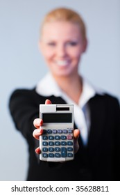 Business woman holding calculator out to the camera with focus on calculator