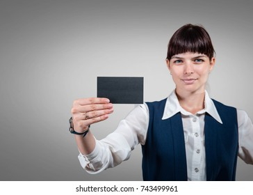 Business woman holding card in hands on gray background. Studio shoot