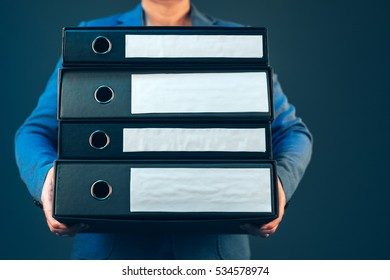 Business woman holding document binders with archived paperwork and other corporate legal sheets, mock up copy space