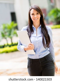 Business woman holding a laptop computer and looking happy