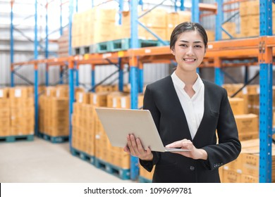 Business woman holding laptop with smiling at warehouse. People working concept.