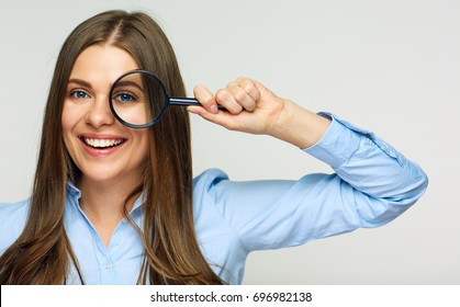 Business woman holding magnifying glass behind eyes. smiling business woman isolated portrait.