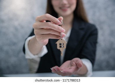 business woman holding Model house Home Loans with money mortgages concept