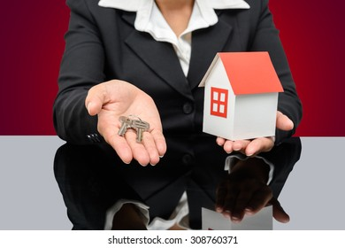 Business woman holding a model house and key. Home insurance concept