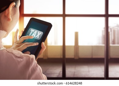 Business woman holding modern tablet with Tax  word on the screen in the office