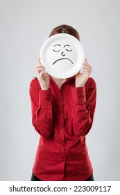 business woman holding a paper plate up to her face with a unhappy face drawn on plate