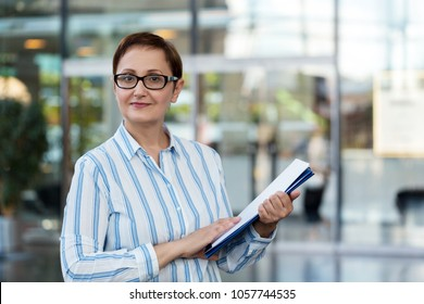 Business woman holding paperwork in the office. Professional portrait of nice middle aged female wearing glasses and shirt, looking at camera and smiling