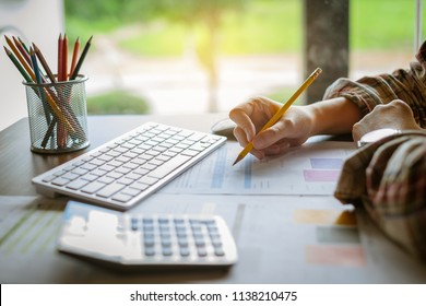 Business woman holding pencil working with financial paperwork. Accounting and Saving concept.