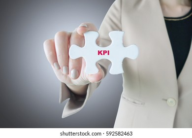 Business woman holding a piece of jigsaw puzzle with word KPI