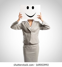 business woman holding a poster with a painted face on it instead of a face, the concept of duplicity in business