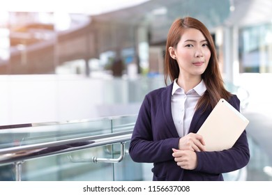 Business woman holding tablet in city with copy space
