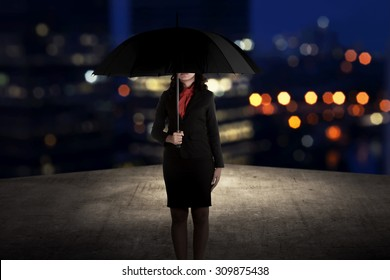 Business woman holding umbrella standing on the rooftop of the building at night time
