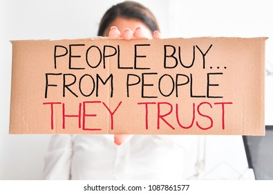 """Business woman holding white card with text """"people buy from people they trust"""""""