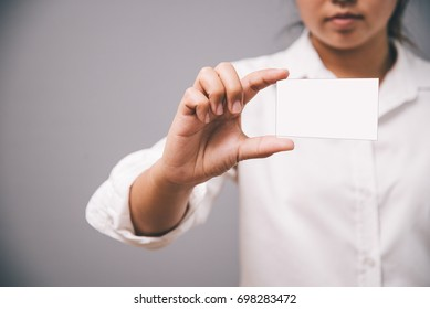 Business Woman holding white color business card in hand with Gray color background.Business concept,Blank Business for your design in woman hand. vintage tone.