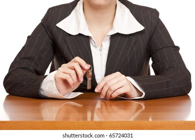 Business woman holds house key for handing over of keys. Isolated on white background.