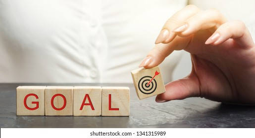 Business woman holds wooden blocks with the word Goal. The concept of achieving business goals. Reaching new heights. Execution of a business plan. Purposefulness. Perseverance. Target. Planning