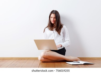 business woman at home with laptop, sitting on the floor