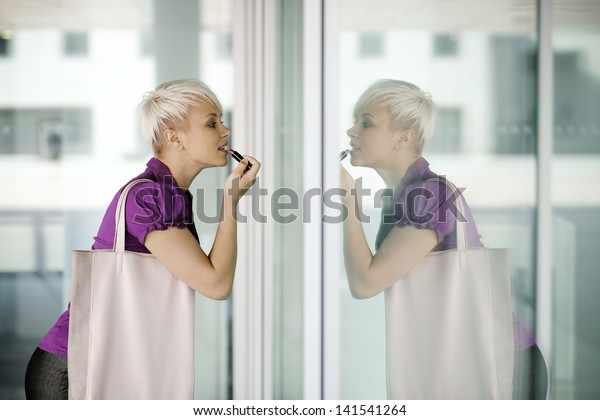 business woman in a hurry applying make up outdoor and looking at office building window