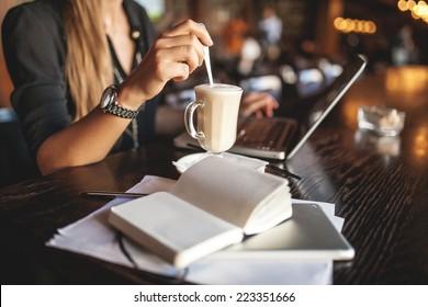 Geschäftsfrau im Haus mit Kaffee und Laptop-Notizen