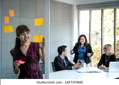 business woman intend at write paper note at glass board and business people discuss marketing plan background, success business concept