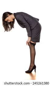 business woman in a jacket and skirt puts on her nylon stockings
