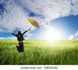 Business woman jumping to blue sky in grassland with rainbow umbrella