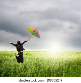 Business woman jumping to raincloud in grassland with rainbow umbrella