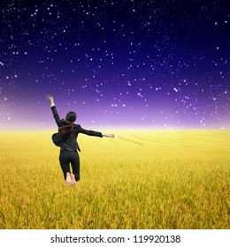 Business woman jumping in Yellow Rice fields and rainclouds