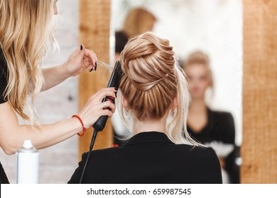 business woman lady boss in beauty salon making hairdress and looking to the mirror