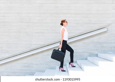business woman with a laptop in her hands up the stairs