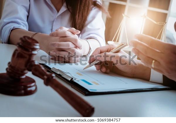 Geschäftsfrau und Rechtsanwälte, die auf Holzschreibtisch im Büro Vertragsunterlagen mit Messing diskutieren. Rechtsberatung, Rechtsberatung, Justiz- und Immobilienkonzept.