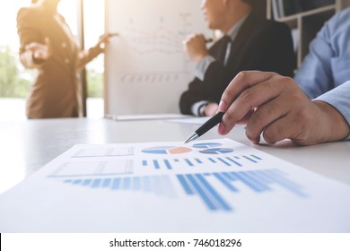 Business woman leader making presentation with her colleagues, pointing to the graph on board and business strategy during meeting in modern office.