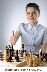 Business woman in a light blue shirt, playing chess