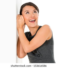 Business woman listening behind walls looking surprised - isolated over white