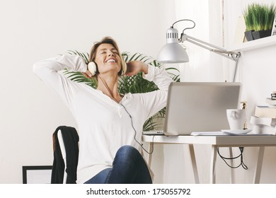 Business woman listening music with headphones.