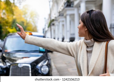 Business woman in London hailing for a black taxi on the street, United Kingdom