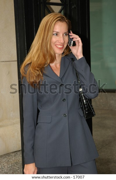 Business woman with long hair on cell phone with big smile