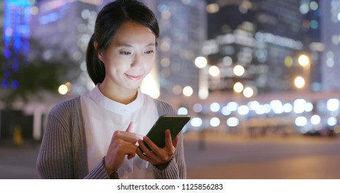 Business woman look at smart phone in city at night