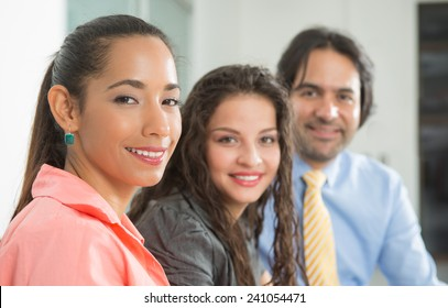 Business woman looking at camera, two other people at the background