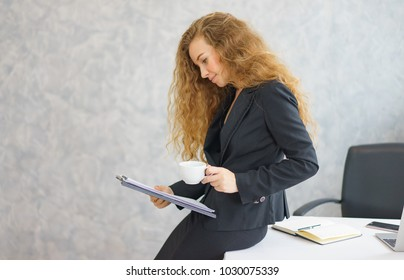 Business woman looking at laptop computer in office.Business woman working at office with laptop and documents on her desk.Start up project.she holding document file and cup coffee.