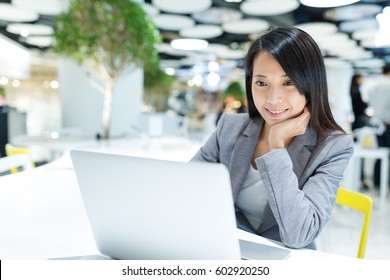 Business woman looking at the notebook computer in co-working place