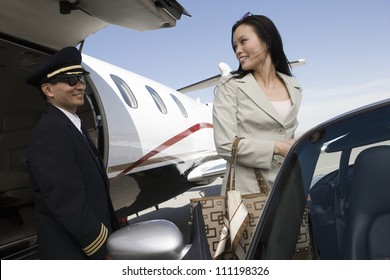 Business woman looking at a pilot when leaving an airplane