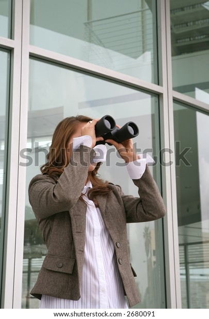 A business woman looking through binoculars with a office building in the background