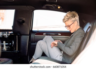Business woman looking at watch in limousine, waiting