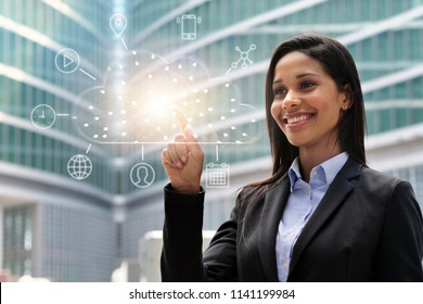 A business woman looks in front of him at the cloud archiving icon that appears with futuristic graphics. Concept of: connection, cyber-security, holography, future.