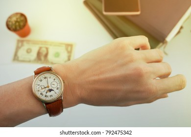 business woman looks at the watch on her wrist, over a white table on which money and diaries lie and dollar