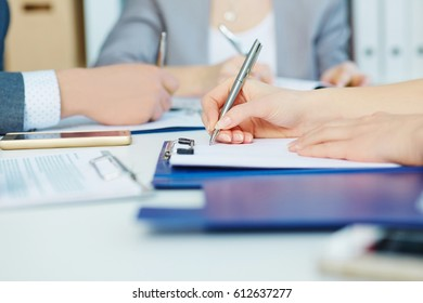 Business woman making notes at office workplace with colleague on the background. Business job offer, financial success, certified public accountant concept.