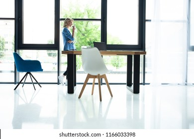 Business woman making a time out sign at the office. Attractive businesswoman drinking a coffee while standing at a window in an office overlooking the city